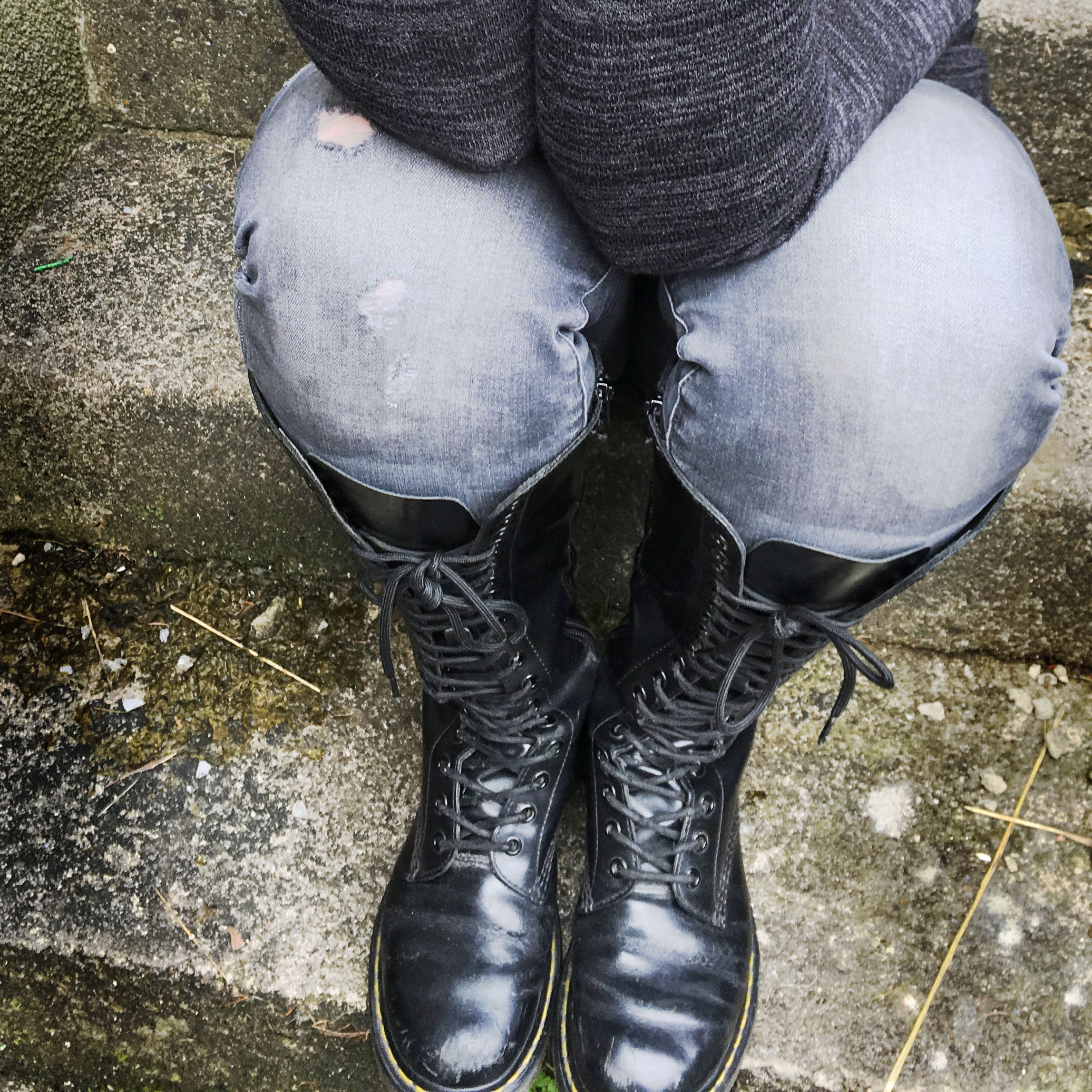 Dr Martens boots and the image of a woman with elbows on her knees showing anxiety