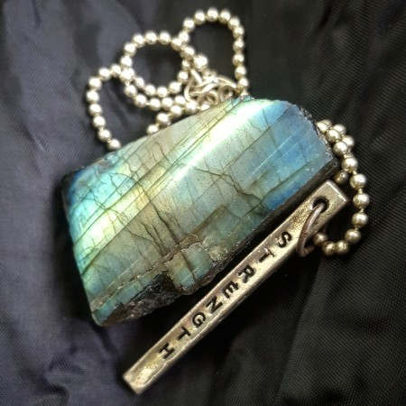 Labradorite gem stone with a necklace with Strength written on it - The Last Krystallos blog