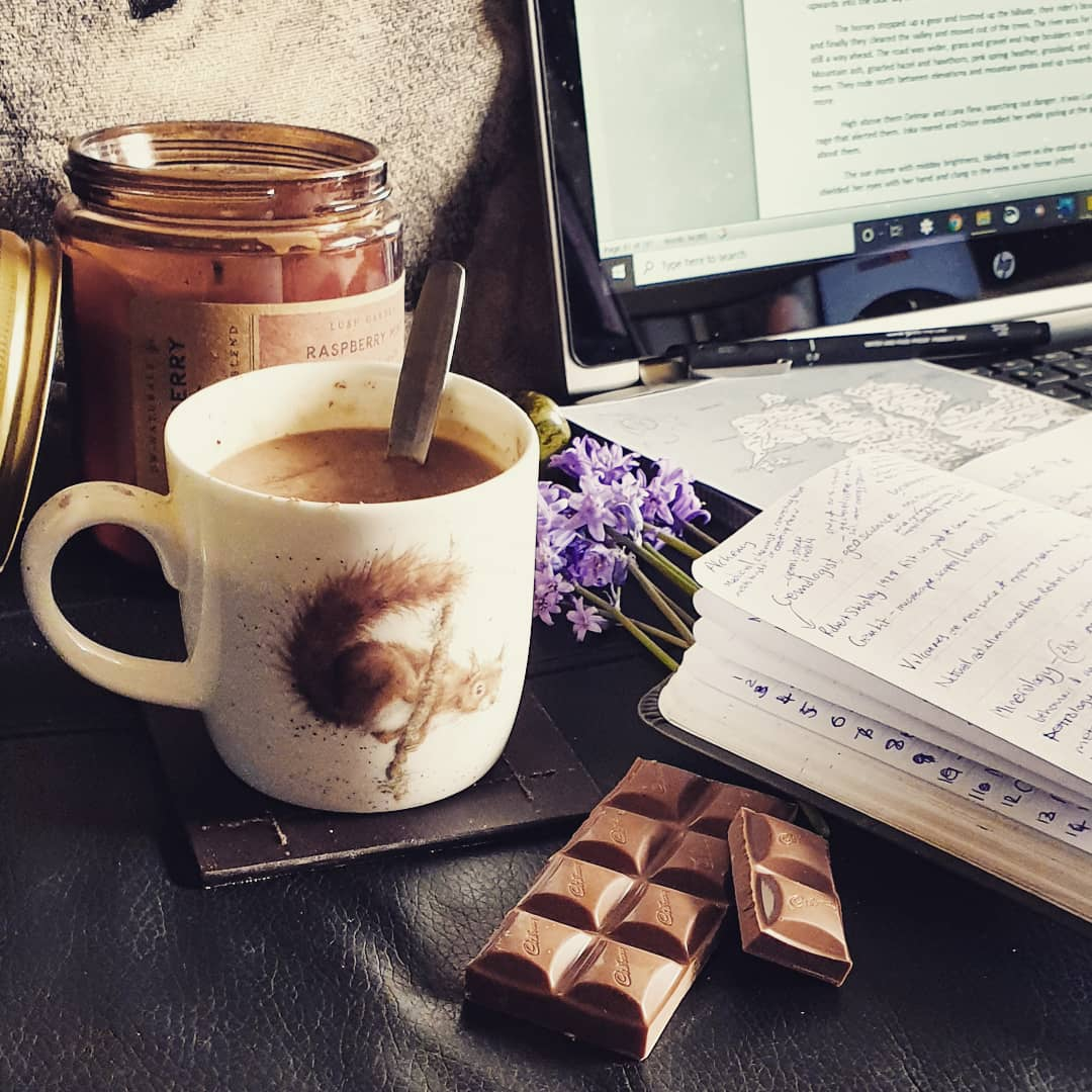 my writing tools - hot chocolate, scented candle, bluebells, chocolate, notebook, laptop