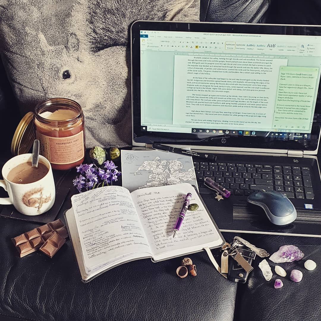 My writing tools - scented candle, hot chocolate, chocolate, laptop, pen, notebooks, bluebells, crystals, hand drawn map, and memory sticks
